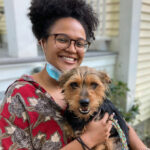 volunteer Jada holding a foster dog outside